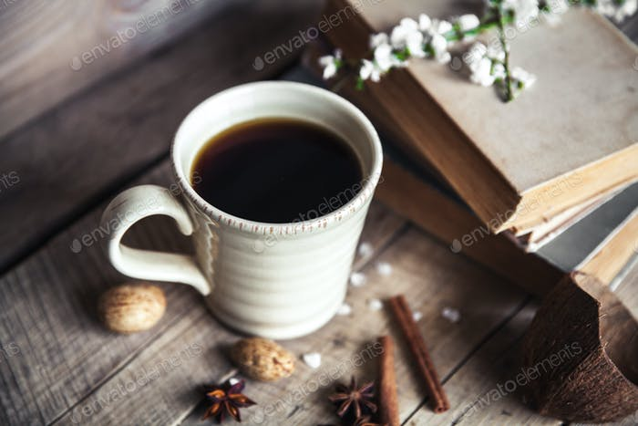 Große Tasse Kaffee auf Vintage-Holzhintergrund. Frühlingsblumen und Bücher