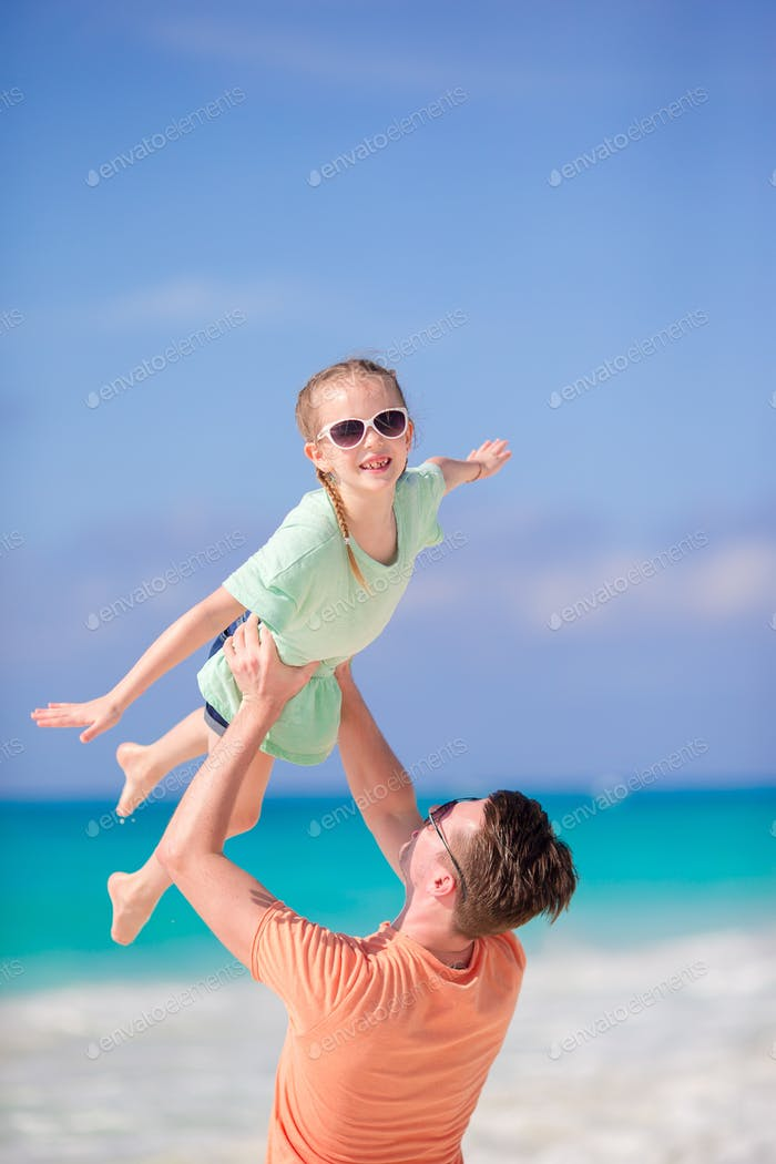 Family beach holiday. Little girl and happy dad having fun during beach vacation