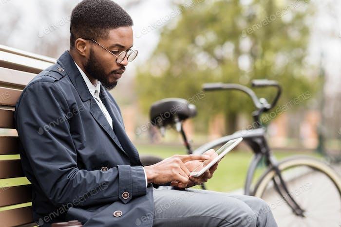 Handsome manager working on digital tablet in park