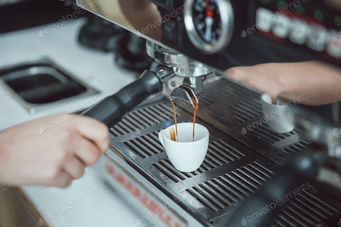 Professional espresso machine pouring fresh coffee into white ceramic cup