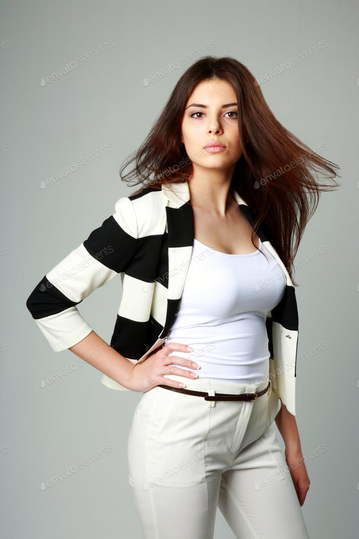 Young beautiful woman in casual clothes on gray background