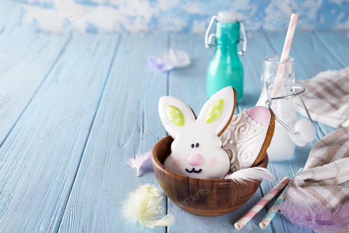 Easter cookies as rabbit and egg in the wooden bowl with milk in glass on wood background