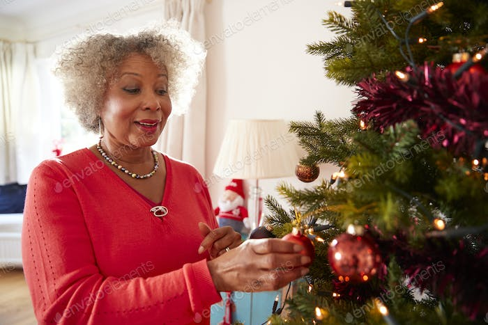 Senior Woman Hanging Decorations On Christmas Tree At Home Together