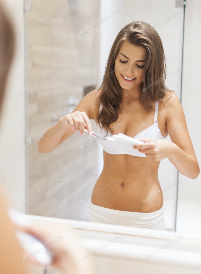 Morning routine by brushing teeth in bathroom