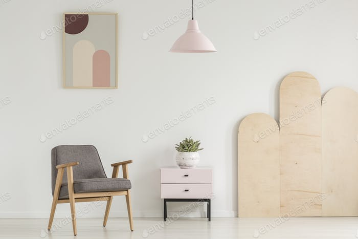 Plant on cabinet next to wooden grey armchair in white flat inte