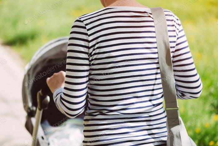 Mutter zu Fuß mit Baby in einem Kinderwagen