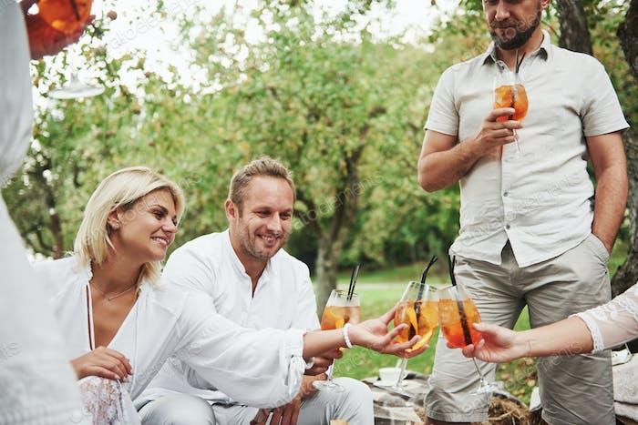 Freunde trinken brandneue frische Cocktails, wenn sie mit Bäumen auf dem Feld sitzen