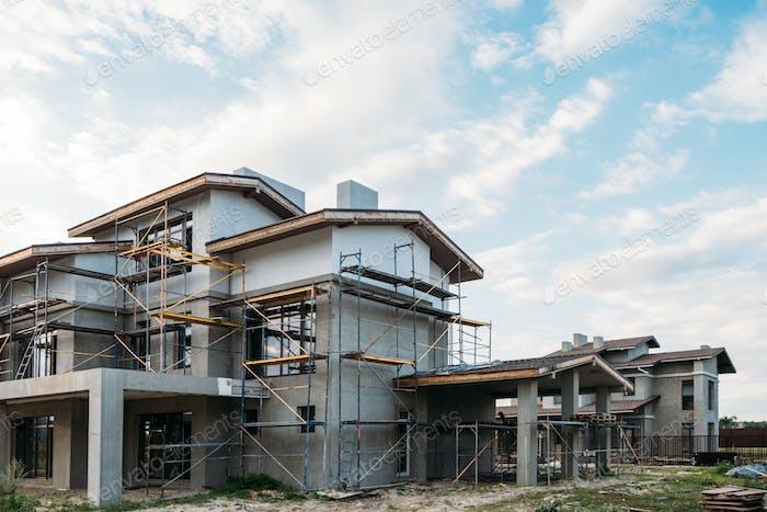 moderner Hochbau mit Gerüsten unter bewölktem Himmel