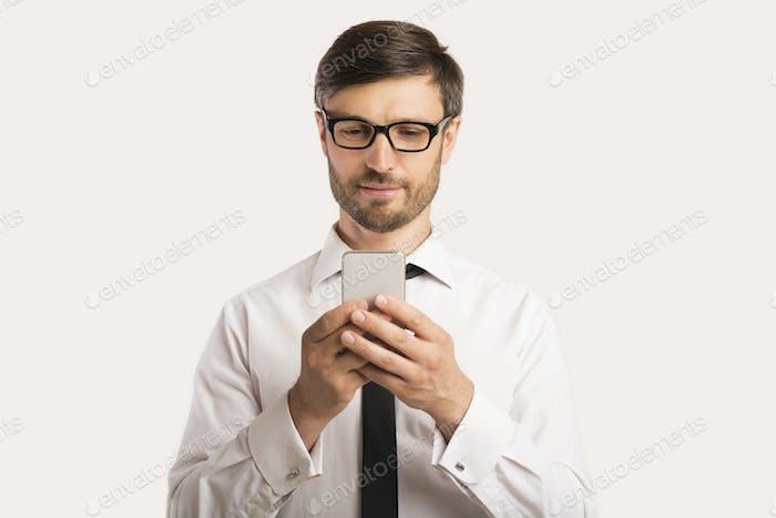Geschäftsmann mit Smartphone stehend über weißem Hintergrund