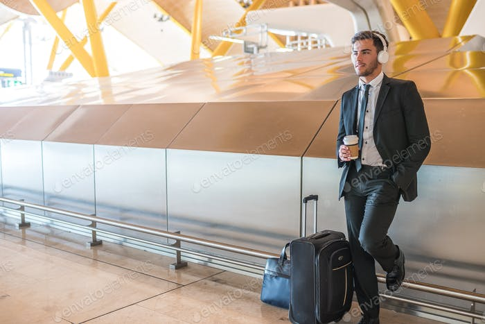 businessman at the airport listening music using his mobile phone waiting his flight with luggage