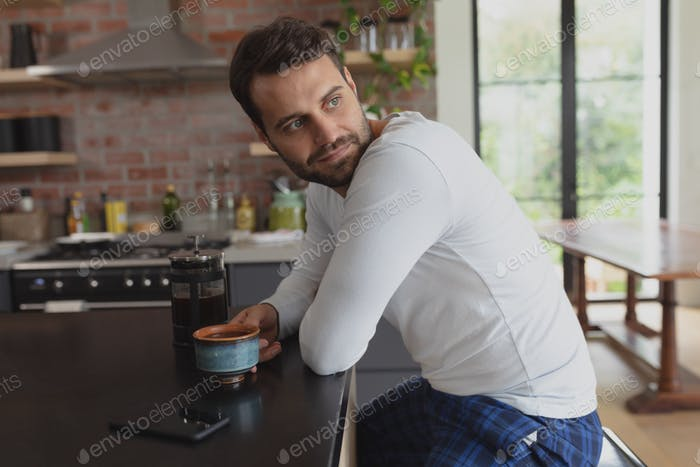 Side view of Caucasian man with coffee cup looking away at dining table in a comfortable home