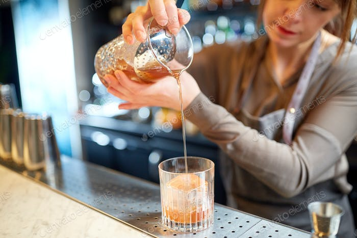 bartender with glass and jug preparing cocktail