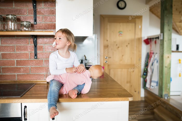 Cute little daughter with her doll sitting on kitchen countertop