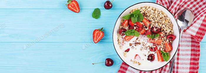 Healthy breakfast - granola, strawberries, cherry, nuts and yogu