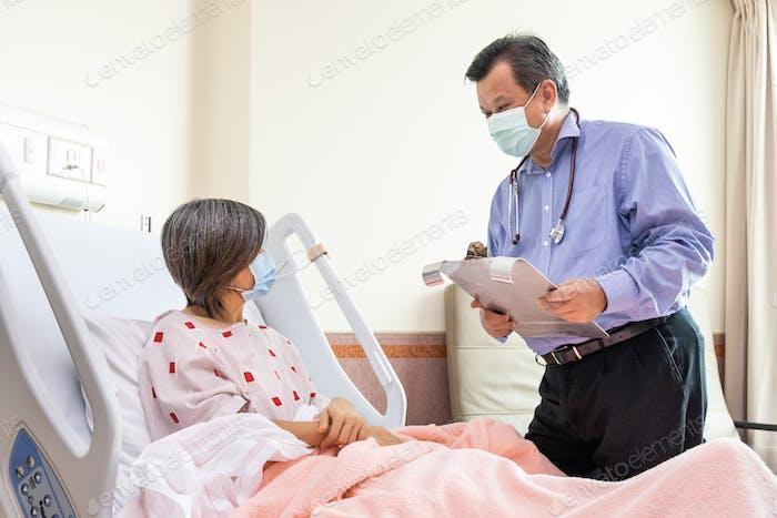 Азиатский врач объясняет веселой пациентке о состоянии здоровья в больнице.