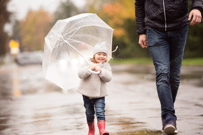 Unrecognizable father with little daughter under the umbrella. R
