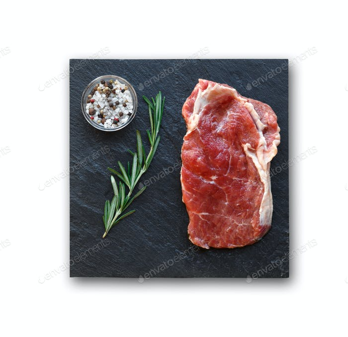 Rib eye steak with spices on slate isolated