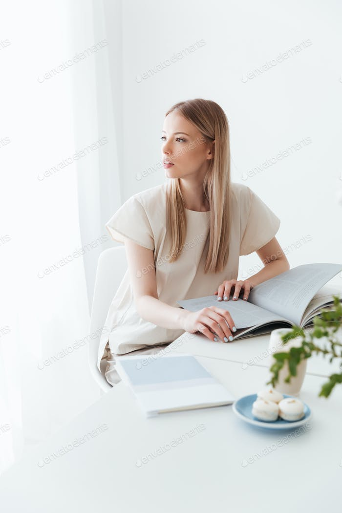 Young woman sitting indoors reading book