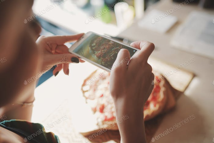 Young woman take photos of pizza