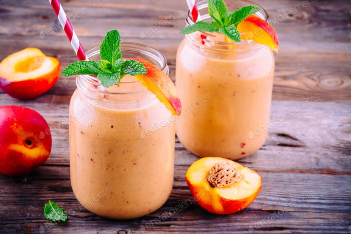 Healthy nectarine smoothies in a mason jar with mint on wooden background