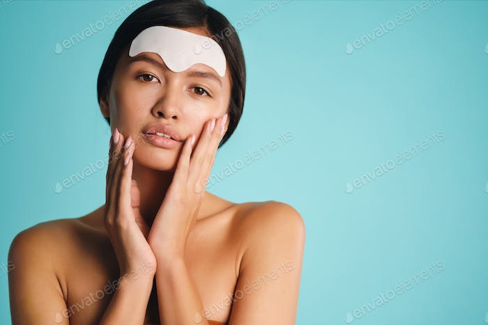 Beautiful Asian brunette girl applying facial mask sensually posing over colorful background