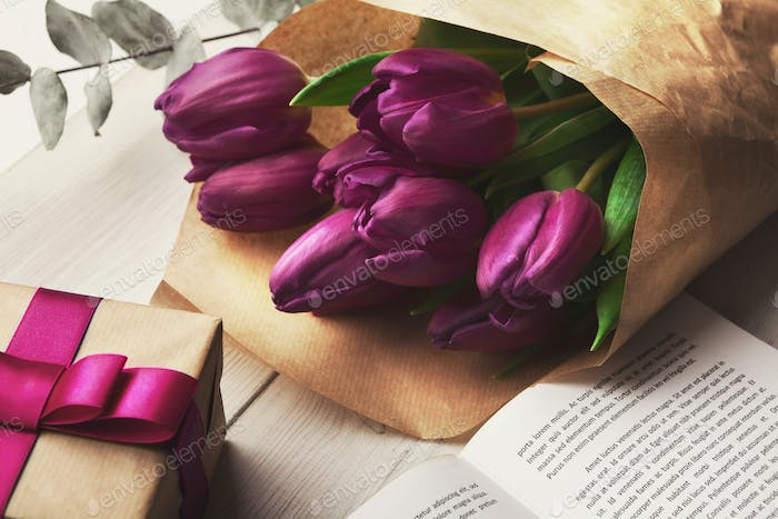 Bouqet of purple tulips and gift box on wooden background