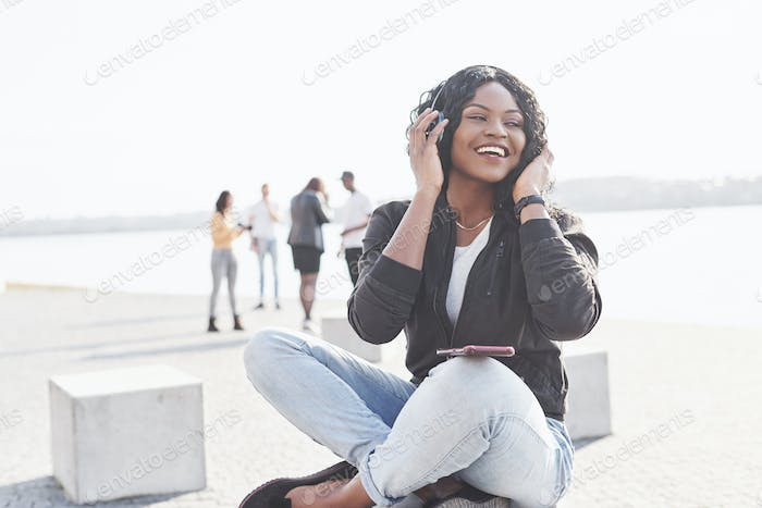 Portrait of a beautiful young pretty African American girl sitting on the beach or lake and