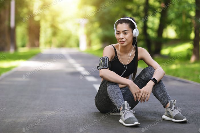 Rest After Training Outdoors. Young Asian Woman In Headphones Sitting On Path