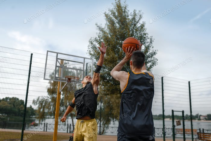 Basketball players play the game on outdoor court