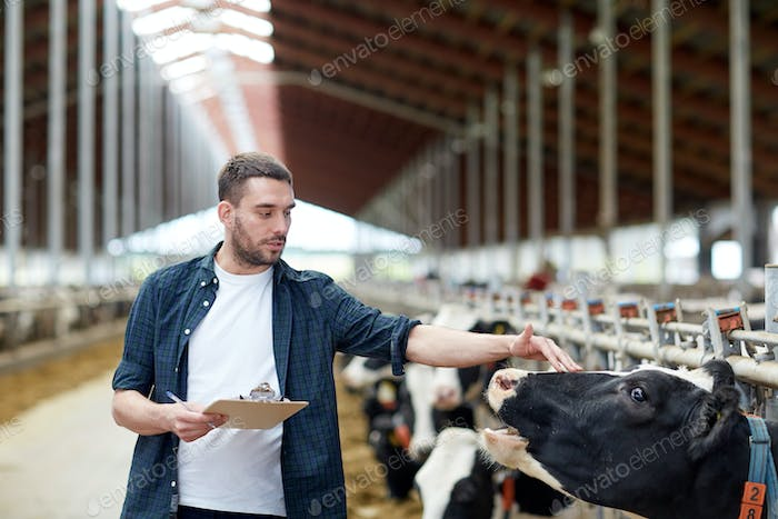 farmer with clipboard and cows in cowshed on farm