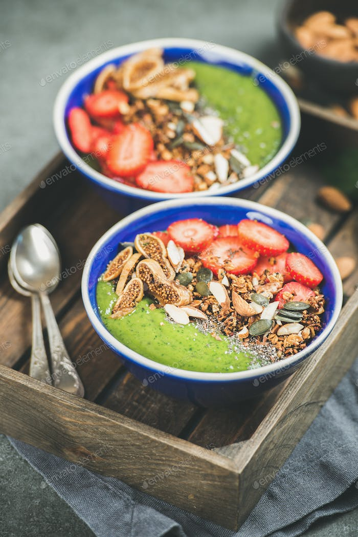 Green smoothie bowls with strawberries, granola, seeds, fruit, nuts