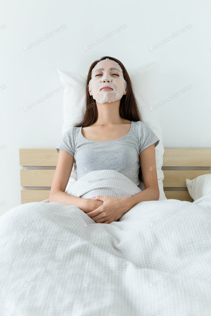 Woman lying down on bed and do masking