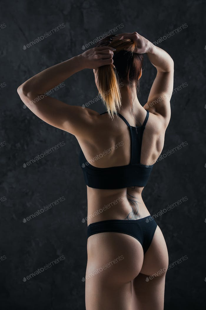 Young fitness girl getting prepared for the workout isolated on dark background