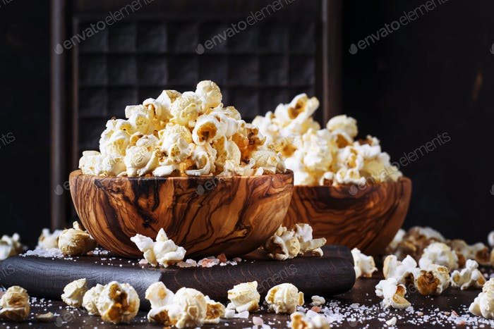Salted popcorn in a wooden bowl, unhealthy food