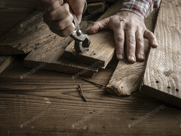 Carpenter removing rusty nails from old wooden planks