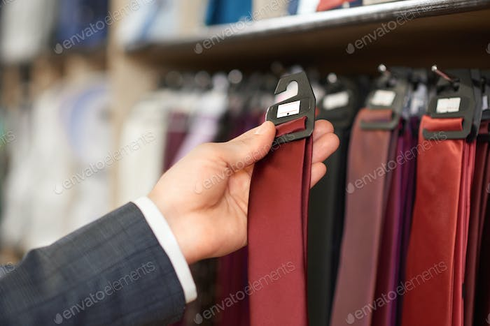 Crop of man's hand holding bordo tie in boutique