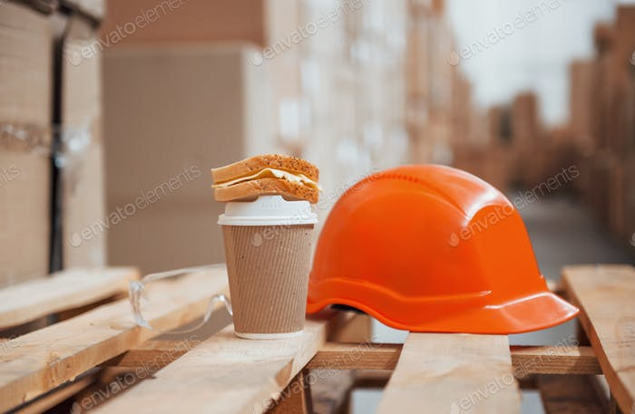 Close up view of orange colored hard hat, cup of drink and sandwich in the warehouse