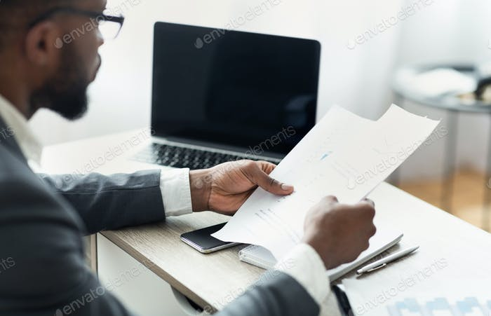 African entrepreneur reading financial reports, working in modern office