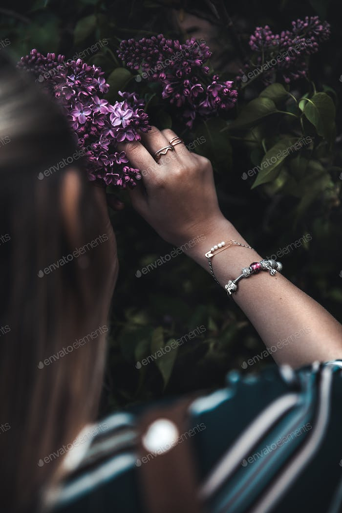 hand holding a dark purple Lilac flower. Springtime. Lilac blooming