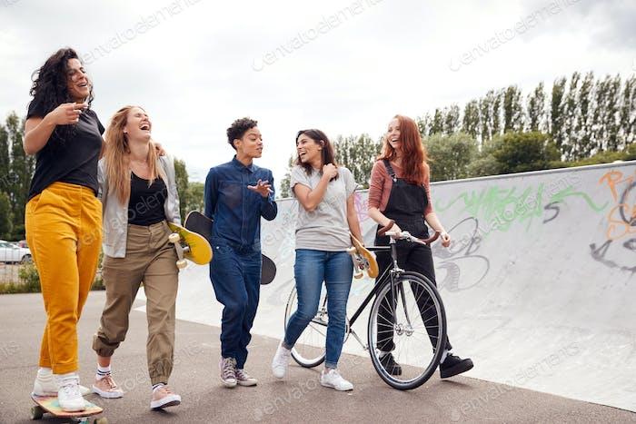 Female Friends With Skateboards And Bike Walking Through Urban Skate Park