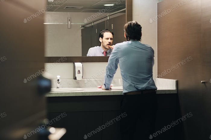 Business Man Brushing Teeth After Lunch Break In Office Bathroom