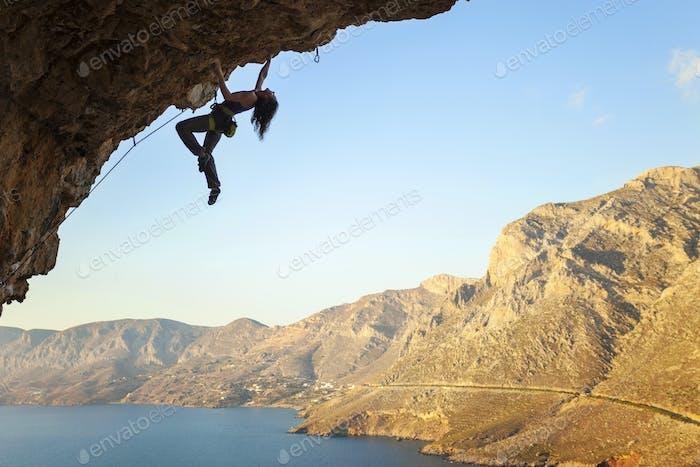 Female rock climber on overhanging cliff, Kalymnos Island, Greece