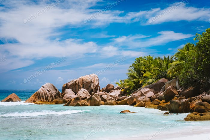 Beautifully shaped granite boulders, shallow tropical lagoon at pristine anse Cocos beach, La Digue