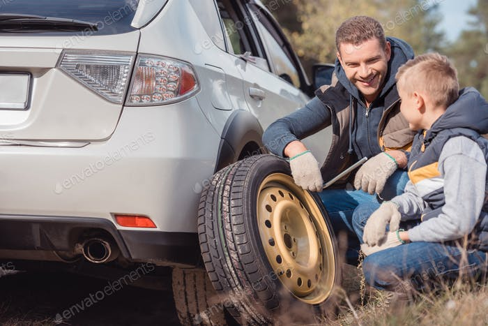 smiling father and son changing car wheel together