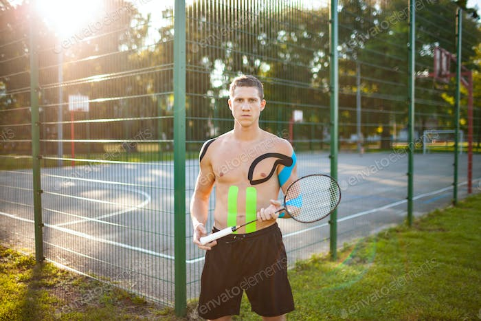 Athlete with kinesiological taping posing with racket outdoors