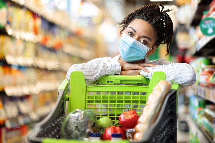 Woman Posing With Shopping Cart Full Of Food In Supermarket