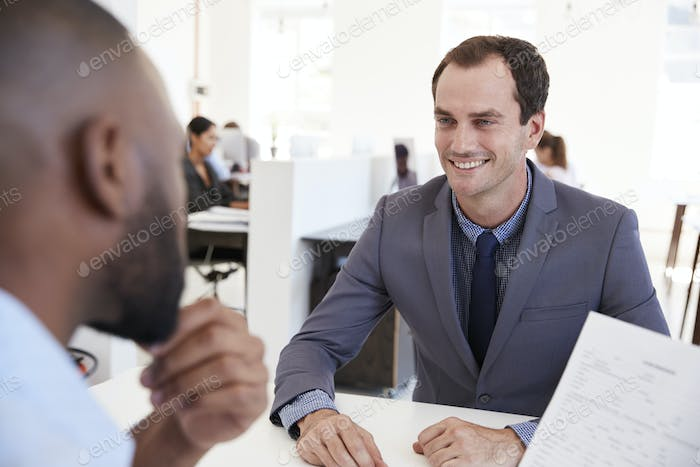 Two young men talking at a meeting in an open plan office