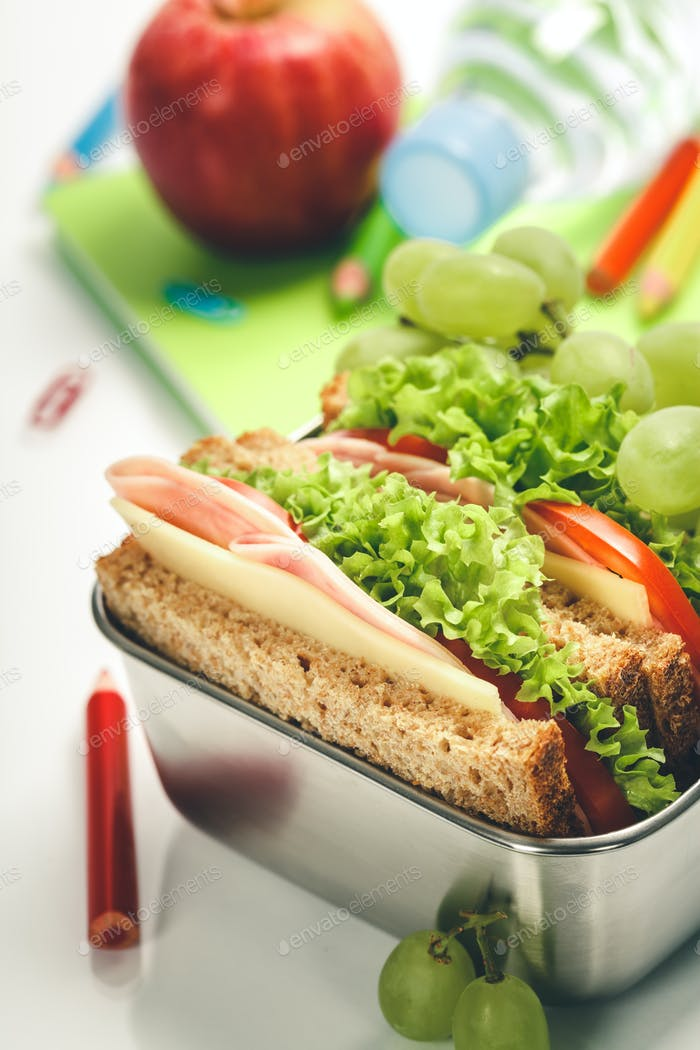 Lunch box with sandwich and fruits, school notebooks, stationery on white background
