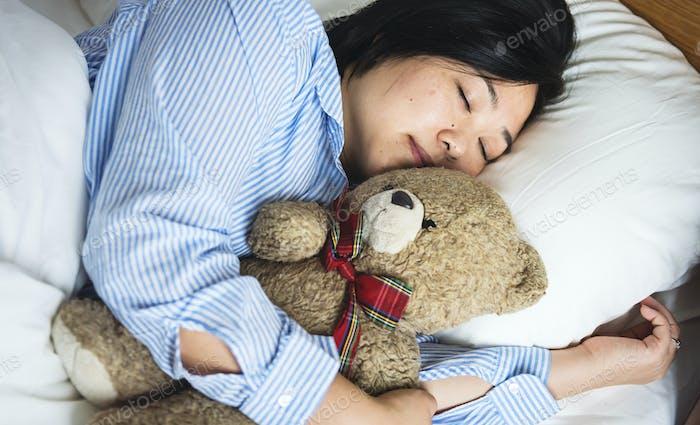 Eine Frau im Bett mit einem Teddybär