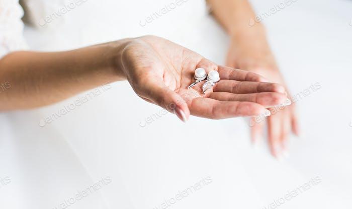 pearl earring in hands